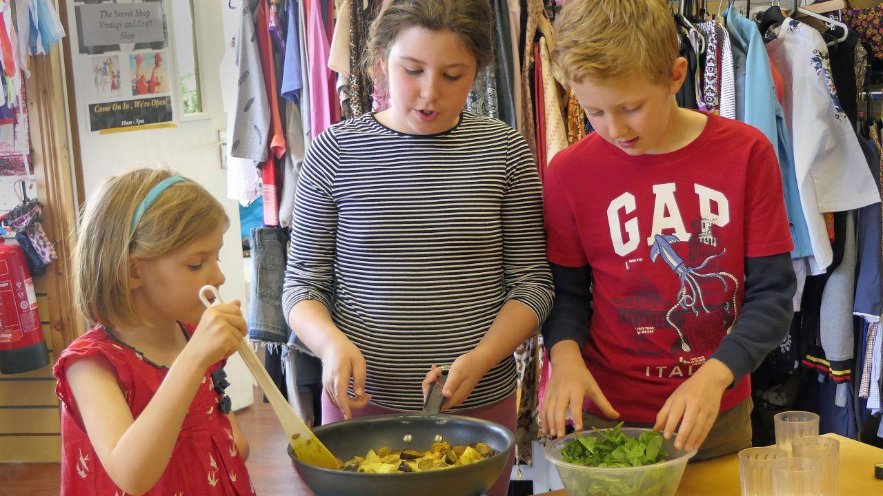 Kids adding ingredients and stirring