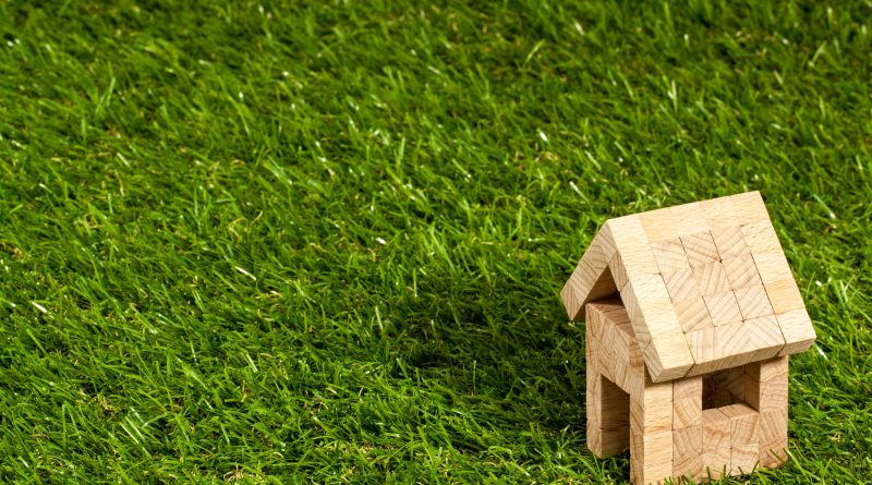 Wooden model house on grass