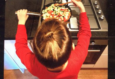 Child stir frying at the stove